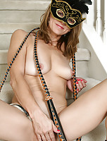 Veronica B plays dressup with a feather mask and a long whip